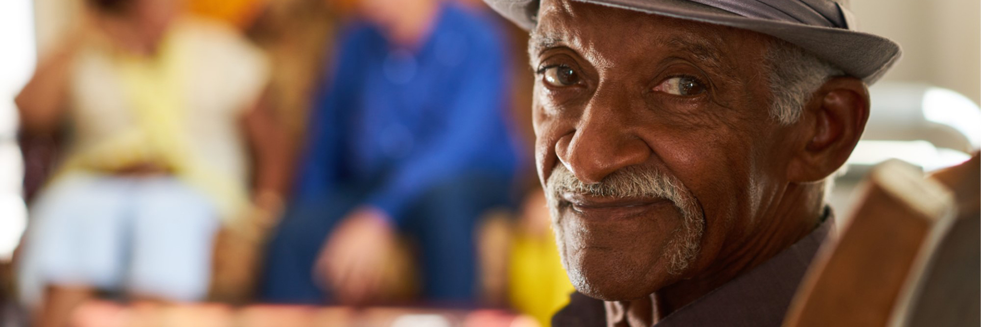 man with mustache and fedora looking at camera